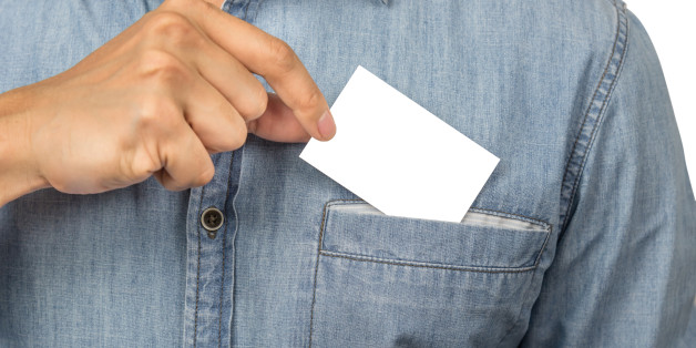 Man with jean shirt taking a blank business card with copyspace from his chest pocket, isolated on white background with clipping path.