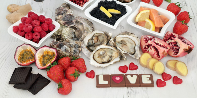 Valentines day aphrodisiac food and drink selection for good  sexual health forming a background over distressed white wood.