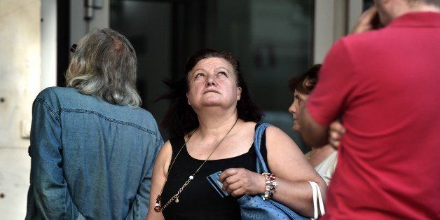 A woman holding a bank card looks up as people queue outside a bank to withdraw cash from an ATM in Athens on July 7, 2015. Eurozone leaders will hold an emergency summit in Brussels on July 7 to discuss the fallout from Greek voters' defiant 'No' to further austerity measures, with the country's Prime Minister Alexis Tsipras set to unveil new proposals for talks.  European Commission head Jean-Claude Juncker said on July 7 that he was against an exit by Greece from the euro, even though Greeks massively rejected bailout terms in a referendum two days prior. AFP PHOTO / ARIS MESSINIS        (Photo credit should read ARIS MESSINIS/AFP/Getty Images)