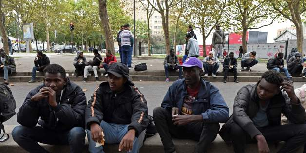 Migrants eat food distributed by the Utopia 56 association in a street of Paris on October 11, 2017.Unprecedented waves of migration are affecting the world today with record numbers of people escaping war-torn regions, poverty, persecution and natural disasters. That influx of people is just a fraction of the record 65.6 million people who were either refugees, asylum seekers or internally displaced around the world by the end of 2016, according to the UN refugee agency. / AFP PHOTO / CHRISTOPH
