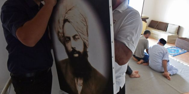 Members of Algeria's small Ahmadi community  put up a photo of Mirza Ghulam Ahmad (1835-1908) the founder of the Ahmadiyya movement, a reformist Islamic movement which is accused of heresy by Islamist extremists and targeted by the authorities, at a house in Tilpasi, west of Algiers, on June 30, 2017.  Founded in late 19th-century India, the Ahmadiyya movement follows the teachings of Mirza Ghulam Ahmad, an Indian Muslim they believe to be the long-awaited Islamic messiah. It is anathema to traditional Islamic thinking, and Ahmadis living in many Muslim-majority countries have faced persecution and physical violence.   / AFP PHOTO / RYAD KRAMDI        (Photo credit should read RYAD KRAMDI/AFP/Getty Images)