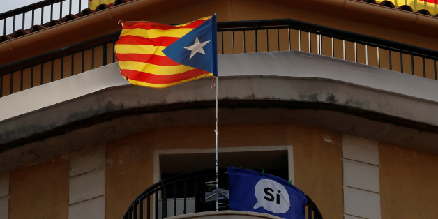 """An Estelada (Catalan separatist flag), banner that reads """"Yes"""", and Spanish flag hang from balconies in Barcelona, Spain, October 14, 2017. REUTERS/Gonzalo Fuentes"""