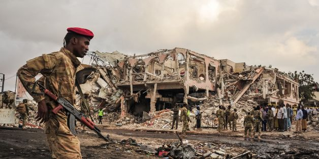 TOPSHOT - EDITORS NOTE: Graphic content / Somali soldiers patrol on the scene of the explosion of a truck bomb in the centre of Mogadishu, on October 15, 2017.A truck bomb exploded outside a hotel at a busy junction in Somalia's capital Mogadishu on October 14, 2017 causing widespread devastation that left at least 20 dead, with the toll likely to rise. / AFP PHOTO / Mohamed ABDIWAHAB        (Photo credit should read MOHAMED ABDIWAHAB/AFP/Getty Images)