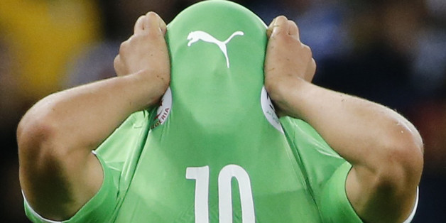 Algeria's Sofiane Feghouli covers his face with his jersey as he reacts to his team's loss at the end of their 2014 World Cup round of 16 game against Germany at the Beira Rio stadium in Porto Alegre June 30, 2014. REUTERS/Edgard Garrido (BRAZIL  - Tags: SOCCER SPORT WORLD CUP TPX IMAGES OF THE DAY)