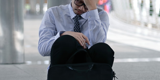 Portrait of frustrated stressed young Asian man sitting on the floor of sidewalk office and feeling tired with job
