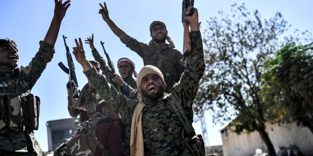 TOPSHOT - Members of the Syrian Democratic Forces (SDF), backed by US special forces, celebrate at the frontline in the Islamic State (IS) group jihadists crumbling stronghold of  Raqa on October 16, 2017 US-backed fighters battled  hundreds of Islamic State group jihadists holed up in the last pockets of Syria's Raqa, as the former extremist stronghold stood on the verge of capture. / AFP PHOTO / BULENT KILIC        (Photo credit should read BULENT KILIC/AFP/Getty Images)