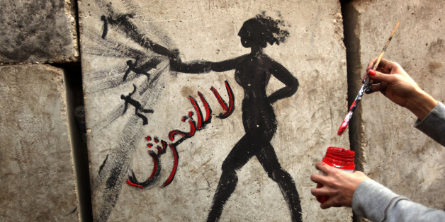 An Egyptian activist draws graffiti depicting a woman and reading in Arabic: 'No to Sexual Harassement' on a wall outside the presidential palace in Cairo on December 14, 2012. Egypt's mainly secular opposition gathered for last-ditch protests against a new constitution it slams as divisive, but on the eve of a referendum it held back from urging a boycott. AFP PHOTO/PATRICK BAZ        (Photo credit should read PATRICK BAZ/AFP/Getty Images)