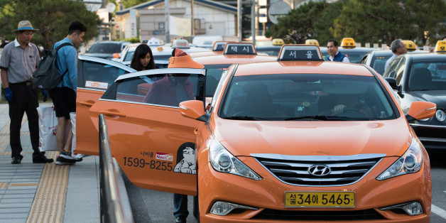 Passengers board taxis outside Seoul Station in Seoul, South Korea, on Monday, May 25, 2015. South Korea is scheduled to release revised first-quarter gross domestic product figures on June 4. Photographer: SeongJoon Cho/Bloomberg via Getty Images