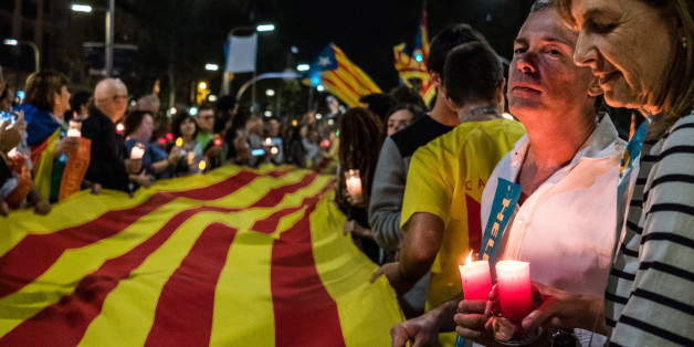 BARCELONA, SPAIN - 2017/10/17: A large flag of Catalonia is seen surrounded by demonstrators holding candle during a protest?Demonstrators took over the streets during the second protest of the day after the admission in prison of Jordi Cuixart and Jordi Sanchez. Around 200,000 people have gathered in Barcelona to ask for the release of the two political prisoners and sovereigntists leaders in prison handed down by judge Carmen Lamela. The demonstrators have the determination to continue with de
