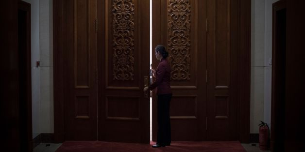 A hostess closes the door of a meeting room at the Great Hall of the People during the Communist Party's 19th Congress in Beijing on October 19, 2017.