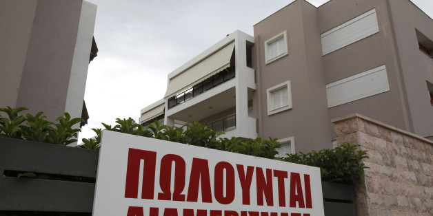 A sign advertises 'apartments for sale,' outside a new luxury housing development in the Glyka Nera suburb of Athens, Greece, on Sunday, Sept. 5, 2010. Greece still faces a 'substantial' default risk as insolvency prevents the nation from repaying its debt when its bailout program expires in three years. Photographer: Kostas Tsironis/Bloomberg via Getty Images