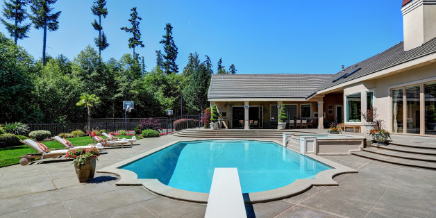 Great backyard with swimming pool and lounge chairs in American Suburban luxury house. Northwest, USA (Symbolbild)