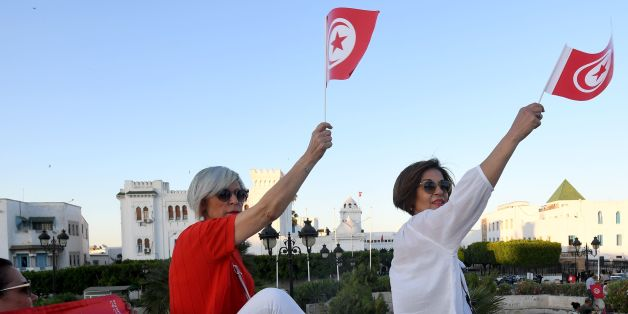 Tunisians hold flags during a demonstration in solidarity with Prime Minister Youssef Chahed in his fight against corruption on May 26, 2017 in front of the prime ministry offices. Tunisian authorities froze the assets of eight businessmen suspected of corruption, including some already under house arrest. Tunisia declared a 'war on corruption' this week after the arrest of three businessmen and a customs officer on suspicion of graft and financing protests in the North African country. / AFP PH