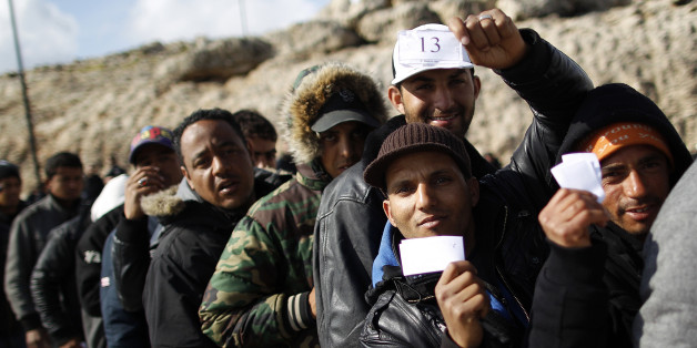People fleeing unrest in Tunisia wait before boarding a cruise liner to a different part of Italy, on the southern island of Lampedusa March 31, 2011. Italian Prime Minister Silvio Berlusconi promised to clear thousands of illegal Tunisian migrants from Lampedusa by the weekend after an outcry over a humanitarian crisis on the tiny southern island. REUTERS/Tony Gentile (ITALY - Tags: POLITICS SOCIETY)