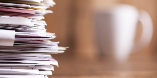 Large stack of multi-colored files and paperwork lie on an office desk.  A white coffee mug in background.  Wooden backdrop.  Copyspace to side.  No people.