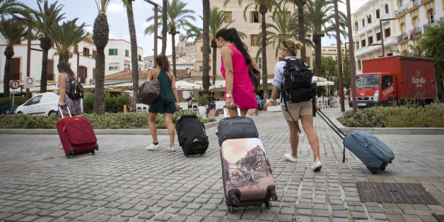 Tourists pull their suitcases in the port of Ibiza, on August 11, 2017.
