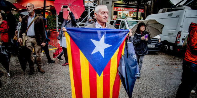 BARCELONA, CATALONIA, SPAIN - 2017/10/19: A man is seen while holding a flag of Catalonia front of the Government Delegation.Despite the heavy rains hundred of people gathered front of the Spanish Government Delegation in Barcelona to demand freedom for the two political prisoners Jordi Cuixart and Jordi Sànchez. This action falls within the days of demonstrations and actions that will take place during the next few weeks due to the application of article 155 that suspends the autonomy and th