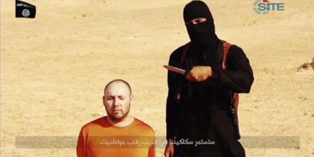 """A masked, black-clad militant, who has been identified by the Washington Post newspaper as a Briton named Mohammed Emwazi, stands next to a man purported to be Steven Sotloff in this still image from a video obtained from SITE Intel Group website February 26, 2015. The """"Jihadi John"""" killer who has featured in several Islamic State beheading videos is Emwazi, a Briton from a middle class family who grew up in London and graduated from college with a degree in computer programming, the Washington"""
