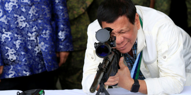 "Philippine President Rodrigo Duterte checks the scope of a 7.62mm sniper rifle during the turnover ceremony of China's urgent military assistance given ""gratis"" to the Philippines, at Clark Air Base, near Angeles City, Philippines June 28, 2017. REUTERS/Romeo Ranoco TPX IMAGES OF THE DAY"