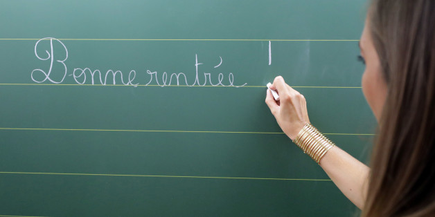 """A teacher writes the phrase """"all the best for going back to school"""" on the blackboard of her classroom on the first day of the new school year at a primary school in Nice, France, September 4, 2017.       REUTERS/Eric Gaillard"""