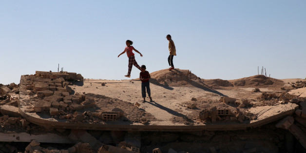 Syrian children are seen playing on a damaged house in Bosra al Sham town, south of Deraa, Syria October 1, 2017. REUTERS/Alaa al Faqir