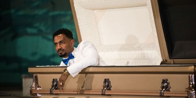 Ethiopian film director Zekarias Mesfin surprises audience by appearing from inside a coffin on the stage of the National Theatre of Ethiopia, during the premiere of his film 'Ewir Amora Kelabi', in Addis Ababa, on October 16, 2017.Zekarias Mesfin spent months making a movie depicting his perilous illegal migration from Ethiopia, but at the film's premiere this week, he arrived in a coffin carried by six white-gloved pallbearers. / AFP PHOTO / Zacharias ABUBEKER        (Photo credit should read