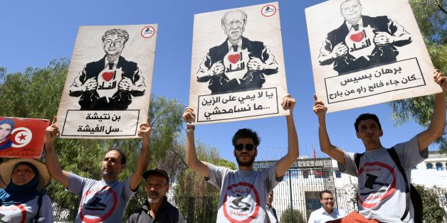 Tunisians chant slogans, wear t-shirts reading in the local Arabic dialect 'I am not forgiving', and carry signs showing cartoons of President Beji Caid Essebsi (C) and his advisers opening their blazers with Arabic text reading 'I [love] corruption' beneath, at a demonstration before parliament in the capital Tunis on July 28, 2017, against a bill that would allow officials being prosecuted for alleged corruption to be amnestied in exchange for reimbursing embezzled funds. / AFP PHOTO / FETHI B