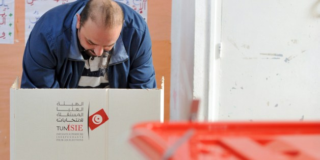A Tunisian man casts his vote on December 21, 2014 at a polling station Ariana near Tunis. The second round vote pits 88-year-old favourite Beji Caid Essebsi, leader of the anti-Islamist Nidaa Tounes party, against incumbent Moncef Marzouki, who held the post through an alliance with the moderate Islamist movement Ennahda. AFP PHOTO / FETHI BELAID        (Photo credit should read FETHI BELAID/AFP/Getty Images)