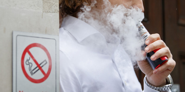 A smoker is engulfed by vapours as he smokes an electronic vaping machine during lunch time in central London on August 9, 2017.