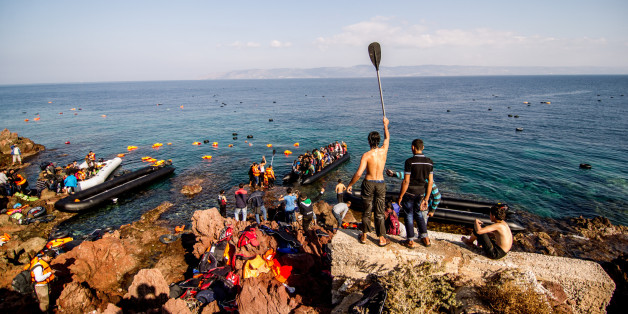 Syrian refugees arrive on a beach covered with life vests and dinghies on the Greek island of Lesbos.