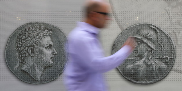 A man walks past pictures of ancient coins in central Athens, Greece, July 13, 2015.  Euro zone leaders agreed on a roadmap to a possible third bailout for near-bankrupt Greece on Monday, but Athens must enact key reforms this week before they will start talks on a financial rescue to keep it in the European currency area. REUTERS/Jean-Paul Pelissier