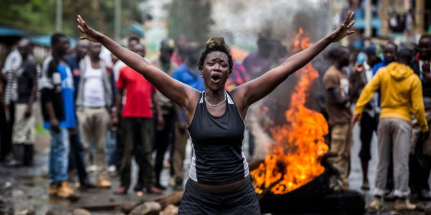 An opposition supporter reacts under the heavy rain in front of a burning barricade in Mathare district, in Nairobi on October 26, 2017, as a group of demonstrators blocked the road and tried to prevent voters from accessing a polling station during presidential elections.Kenyans trickled into polling stations on October 26 for a repeat election that has polarised the nation, amid sporadic clashes as supporters of opposition leader ignored his call to stay away and tried to block voting. / AFP P
