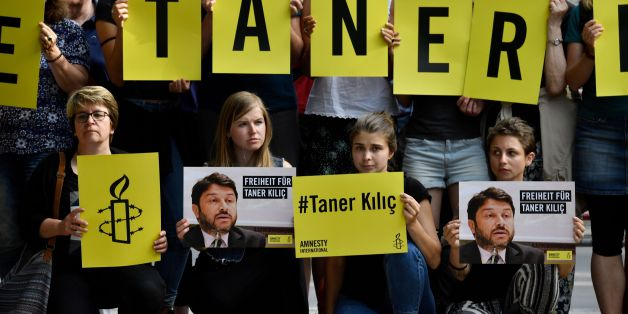 Activists of Amnesty International stage a protest against the detention of the head of Amnesty International in Turkey, Taner Kilic, in front of the Turkish Embassy in Berlin on June 15, 2017.Taner Kilic was arrested in the Turkish province of Izmir along with 22 other lawyers on June 6, 2017 and has been charged with membership of a terrorist organisation and remanded in custody pending trial  / AFP PHOTO / John MACDOUGALL        (Photo credit should read JOHN MACDOUGALL/AFP/Getty Images)