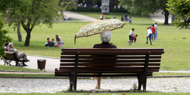 A woman shields herself from the sun with an umbrella at a park in Lisbon June 10, 2013.   REUTERS/Jose Manuel Ribeiro (PORTUGAL - Tags: SOCIETY)