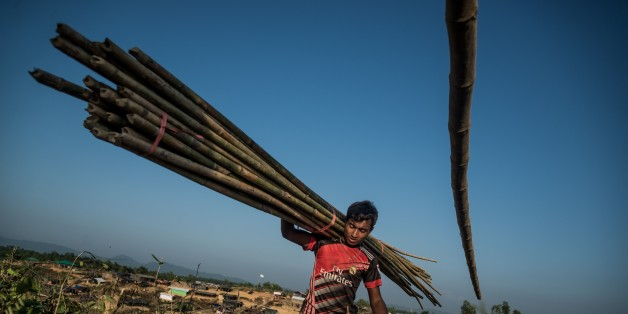 COXS BAZAR, BANGLADESH - OCTOBER 27: A Rohingya Muslim carries bamboo logs at Kutupalong Rohingya refugee camp  in Coxs Bazar, Bangladesh on October 27, 2017. 15,000 Rohingya refugees have taken shelter at Kutupalong refugee camp after fleeing from Myanmar's violence. (Photo by Stringer/Anadolu Agency/Getty Images)