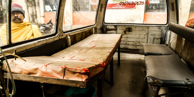 Bhadrapur, Nepal - January 18, 2014: A hospital visitor in eastern Nepal looks through a dilapidated ambulance parked in the compound.
