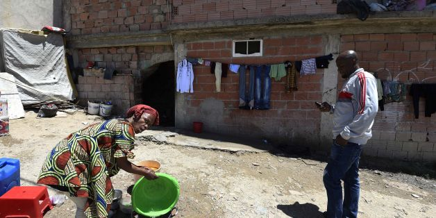 A Sub-Saharan woman does some washing-up at the bottom of a makeshift building, where she lives with other fellow migrants in impoverished conditions, on May 29, 2016, in the capital Algiers.  In the past, Algeria was a land of emigration, millions of its citizens exiled to France, but in recent years it has become a destination country for many West Africans. Nigerians, Malians, Cameroonians, brave the horrors of the Sahara to find refuge in the largest country in Africa, as the crossing to Eur
