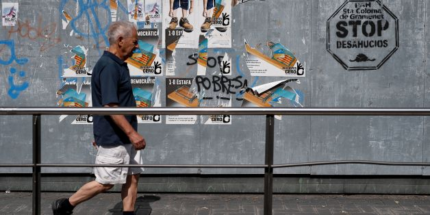 A man walks in front of  pro-referendum posters in Santa Coloma de Gramenet on September 16, 2017.  / AFP PHOTO / PAU BARRENA        (Photo credit should read PAU BARRENA/AFP/Getty Images)