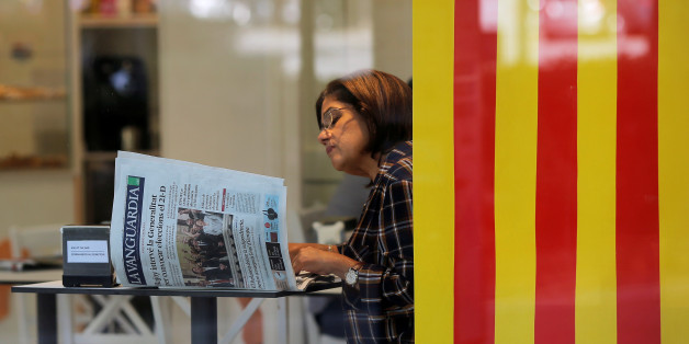A woman reads a newspaper next to a Catalan flag at a coffee shop the day after the Catalan regional parliament declared independence from Spain in Barcelona, Spain, October 28, 2017. REUTERS/Jon Nazca