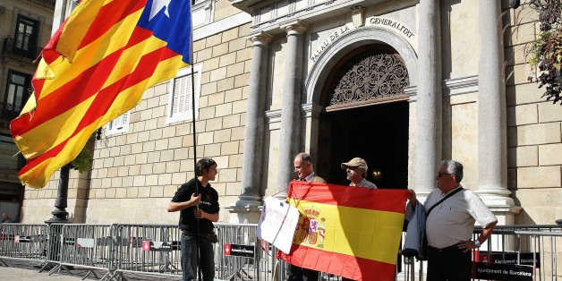 BARCELONA, SPAIN - OCTOBER 30: Some people unfold a Spanish flag as another man waves a Catalan pro-independece flag in front of the 'Generalitat' palace (Catalan government headquarters) in Barcelona on October 30, 2017. Spain enters uncharted and potentially perilous territory today as Madrid moves to take over the running of Catalonia in response to the rebellious region's parliament unilaterally declaring independence.  (Photo by Dursun Aydemir/Anadolu Agency/Getty Images)