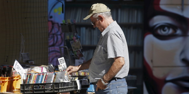 A man looks at used DVDs at a store at Monastiraki area in central Athens, Greece, July 7, 2015. Greece faces a last chance to stay in the euro zone on Tuesday when Prime Minister Alexis Tsipras puts proposals to an emergency euro zone summit after Greek voters resoundingly rejected the austerity terms of a defunct bailout.  REUTERS/Christian Hartmann