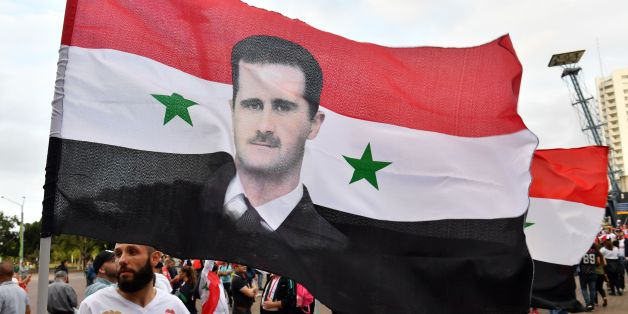 Syrian migirants carry their national flags and pictures of Syrian President Bashar al-Assad jubilate outside the stadium prior to 2018 World Cup football qualifying match between Australia and Syria in Sydney on October 10, 2017. / AFP PHOTO / SAEED KHAN / -- IMAGE RESTRICTED TO EDITORIAL USE - STRICTLY NO COMMERCIAL USE --        (Photo credit should read SAEED KHAN/AFP/Getty Images)