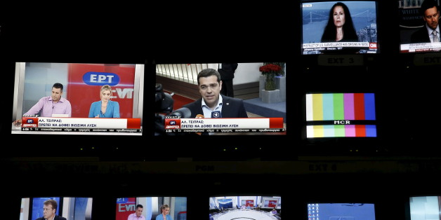 """Greek Prime Minister Alexis Tsipras is seen on a monitor screen (C) at the control room during the first broadcast of state television ERT after its reopening in Athens June 11, 2015. Employees at Greece's state television ERT hugged each other and cried on Thursday as the channel aired its first broadcast in two years, after it was shut down under one of the previous government's most drastic austerity measures. Leftist Prime Minister Alexis Tsipras, who is racing to reach a cash-for-reforms deal with the European Union and IMF, had called ERT's closure """"a great wound"""" of his country's bailout. He made its reopening one of his priorities as part of efforts to roll back cuts demanded by the lenders.  REUTERS/Alkis Konstantinidis"""