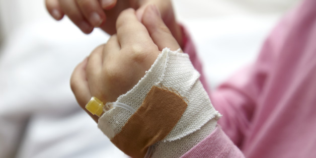Little girl in hospital with an IV drip line. Only her hands can be seen. Full frame shot, horizontal.
