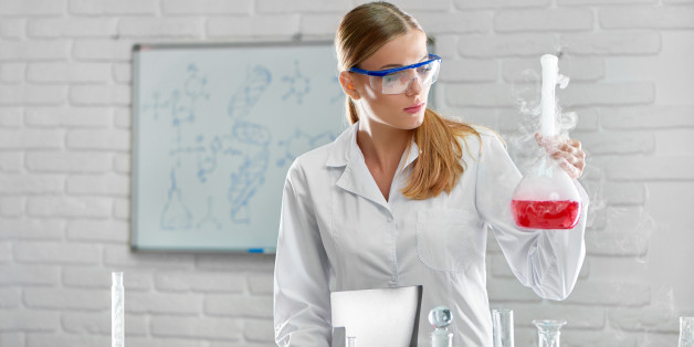 Beautiful young professional female scientist carrying out an experiment with smoking liquids at the laboratory making notes professionalism multitasking development people science concept.