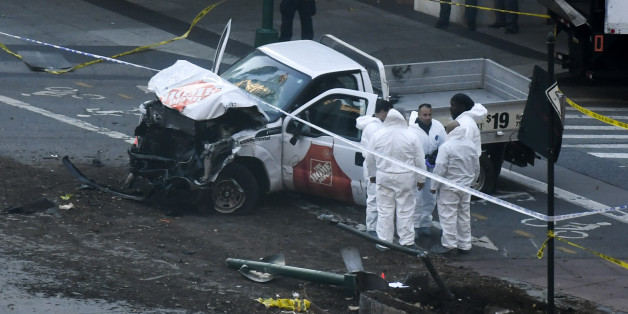 Investigators inspect a truck following a shooting incident in New York on October 31, 2017.  Several people were killed and numerous others injured in New York on Tuesday after a vehicle plowed into a pedestrian and bike path in Lower Manhattan, police said. 'The vehicle struck multiple people on the path,' police tweeted. 'The vehicle continued south striking another vehicle. The suspect exited the vehicle displaying imitation firearms & was shot by NYPD.' / AFP PHOTO / DON EMMERT        (Photo credit should read DON EMMERT/AFP/Getty Images)