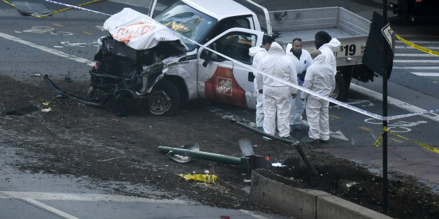 Investigators inspect a truck following a shooting incident in New York on October 31, 2017. Several people were killed and numerous others injured in New York on Tuesday after a vehicle plowed into a pedestrian and bike path in Lower Manhattan, police said. 'The vehicle struck multiple people on the path,' police tweeted. 'The vehicle continued south striking another vehicle. The suspect exited the vehicle displaying imitation firearms & was shot by NYPD.' / AFP PHOTO / DON EMMERT        (Photo