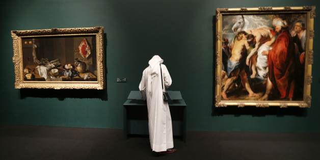 An Emirati visitor stands near a painting (R) by Flemish Baroque painter Jacob Jordaens that is part of 130 artworks featured at the first large-scale presentation of the permanent collection of Abu Dhabi's planned Louvre Museum, at a venue on the Saddiyat Island where the museum will be built off the Emirati capital, on April 21, 2013. The Louvre Abu Dhabi, which opened it's first permanent collection to the public on April 21, is the largest of France's overseas cultural project, Filippetti to