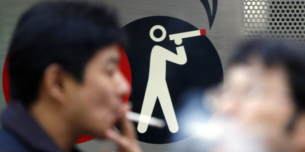 Smokers smoke cigarettes at a smoking area in Tokyo February 8, 2007. Japan Tabacco Inc. posted a 9 percent rise in profit for the nine month to December, led by growth in overseas sales and price hike, and it raised its full-year forecast by 3 percent to above market expectations.   REUTERS/Issei Kato (JAPAN)