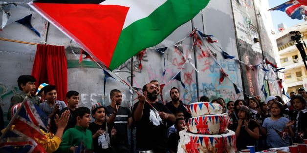 A Palestinian man flies his national flag above a cake bearing images of the Union Jack as children from the al-Aida refugee camp attend an event held by secretive British street artist Banksy to apologise for the 100th anniversary of the Balfour Declaration on November 1, 2017 at his Walled-Off Hotel in Bethlehem in the occupied West Bank.The queen revealed a plaque carved in stone saying 'Er, Sorry,' playing on the common initials for Elizabeth Royal. / AFP PHOTO / AHMAD GHARABLI        (Photo